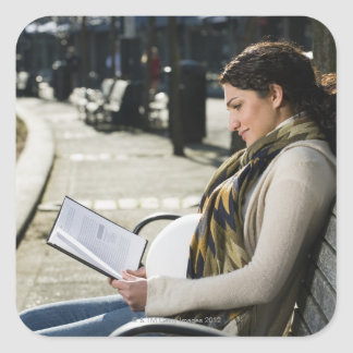 Pregnant Middle Eastern woman reading on park Square Stickers