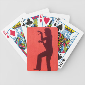 Profile shadow of woman on red wall bicycle playing cards