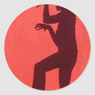 Profile shadow of woman on red wall classic round sticker