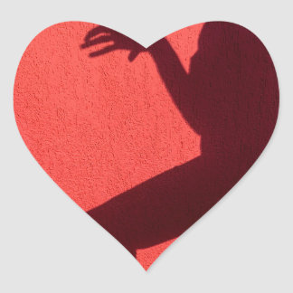 Profile shadow of woman on red wall heart sticker