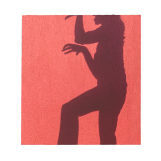 Profile shadow of woman on red wall notepad