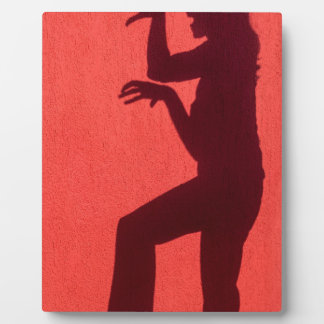 Profile shadow of woman on red wall plaque
