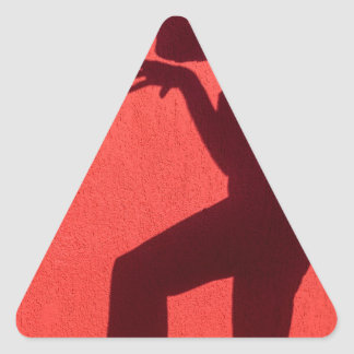 Profile shadow of woman on red wall triangle sticker