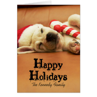 Puppy sleeps on sofa with christmas toys greeting card