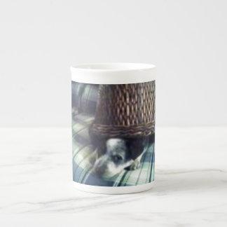 Puppy under basket tea cup