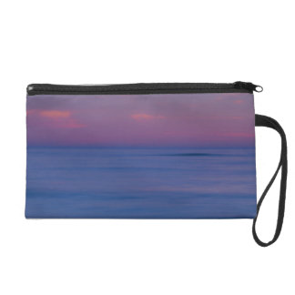 Purple-colored sunrise on ocean shore 2 wristlet clutch