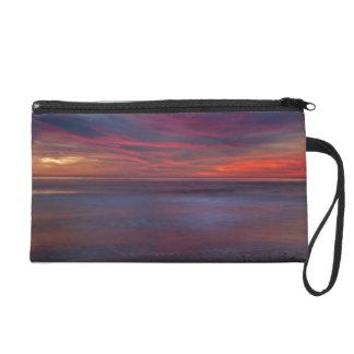 Purple-colored sunrise on ocean shore wristlet purse