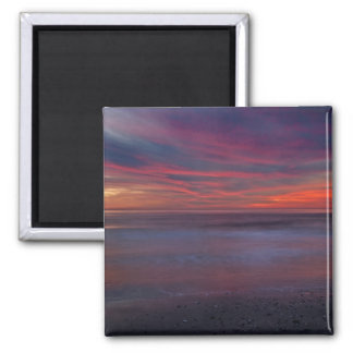 Purple-colored sunrise on ocean shore square magnet