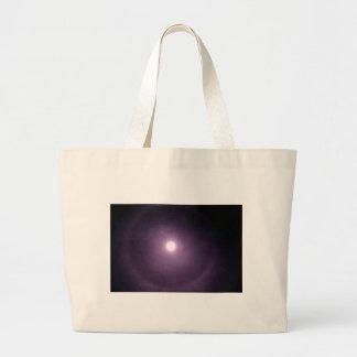 Purple rings around full moon tote bags