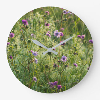 Purple wild flowers in a green meadow large clock