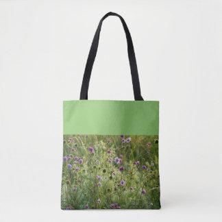 Purple wild flowers in a green meadow tote bag