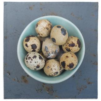 Quails eggs in a green bowl napkin