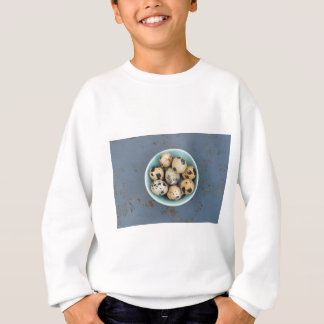 Quails eggs in a green bowl sweatshirt