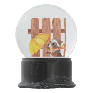 racoon with umbrella walking by fence snow globe