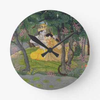 Radha and Krishna embrace in a grove of flowering Wall Clock