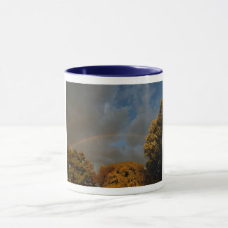 Rainbow over the trees in blue sky mug