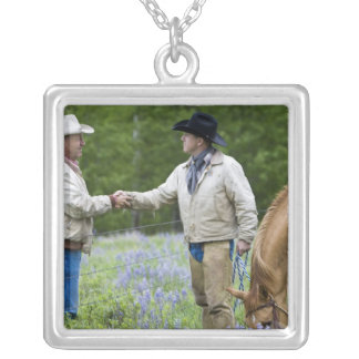 Ranchers shaking hands across the fencing in square pendant necklace