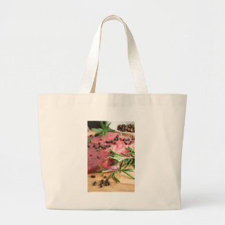 Raw beef with herbs and spices at the kitchen large tote bag