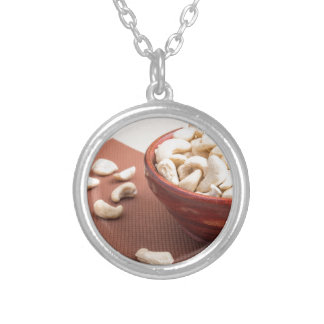 Raw cashew nuts for vegetarian food closeup silver plated necklace
