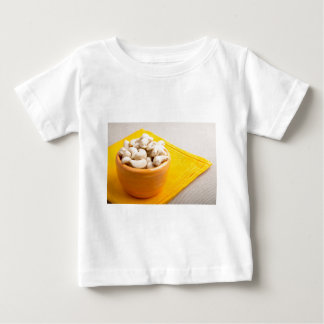 Raw cashew nuts in a small orange cup closeup baby T-Shirt