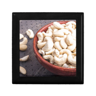 Raw cashew nuts in brown bowl on fabric background gift box