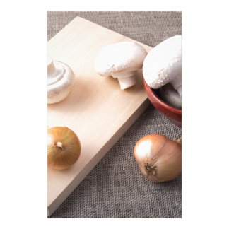 Raw champignon mushrooms and onions on the table stationery