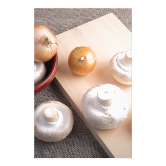 Raw champignon mushrooms and onions stationery