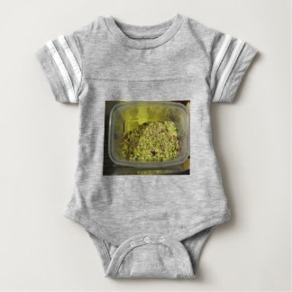 Raw chopped pistachios in a plastic food pan baby bodysuit