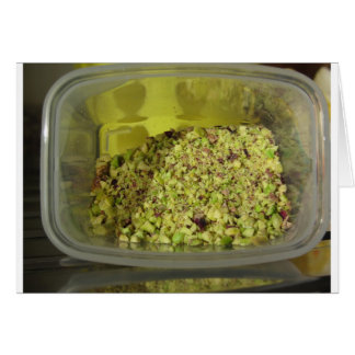 Raw chopped pistachios in a plastic food pan card