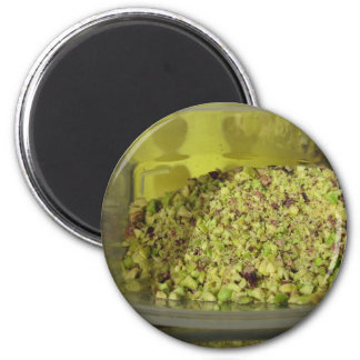 Raw chopped pistachios in a plastic food pan magnet