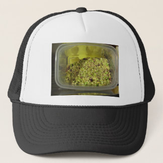 Raw chopped pistachios in a plastic food pan trucker hat