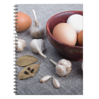 Raw eggs and garlic and spices on the kitchen notebook