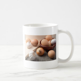 Raw eggs, onions and garlic on a background coffee mug