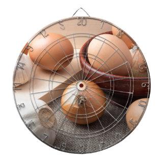 Raw eggs, onions and garlic on a background dartboard