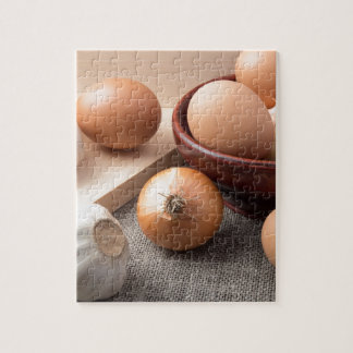 Raw eggs, onions and garlic on a background jigsaw puzzle