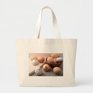Raw eggs, onions and garlic on a background large tote bag