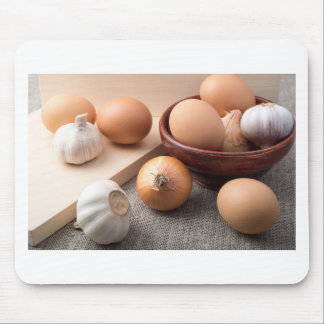 Raw eggs, onions and garlic on a background mouse pad