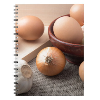 Raw eggs, onions and garlic on a background note book