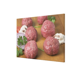 Raw meatballs on a cutting board stretched canvas prints