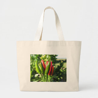 Red and green peppers hanging on the plant large tote bag