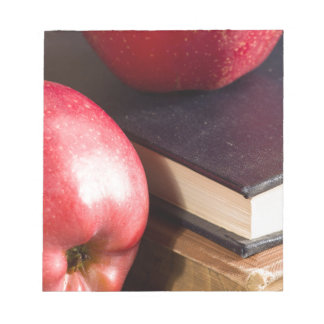 Red apples and old vintage book notepad