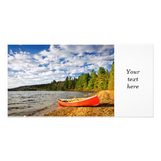 Red canoe on lake shore picture card