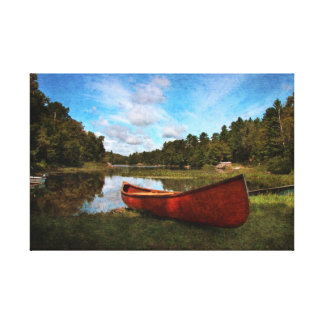 Red canoe on the lake bank canvas print