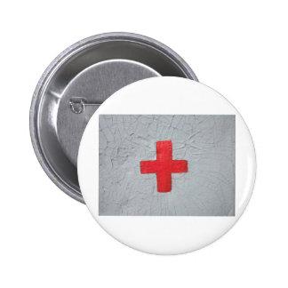 Red cross on grey flaking paint knapp med nål