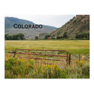 red gate by a prairie in Colorado Postcard