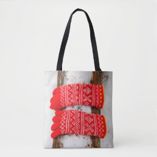 Red knitted gloves in snow tote bag
