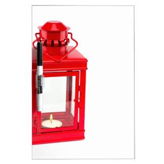 Red lantern with burning tealight on white dry erase board