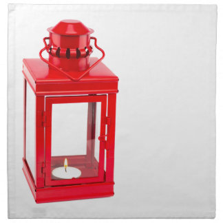 Red lantern with burning tealight on white napkin