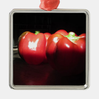 Red peppers illuminated by sunshine in the dark metal ornament