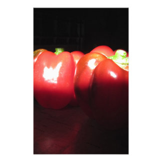 Red peppers illuminated by sunshine in the dark stationery